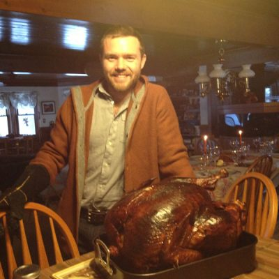 Patrick Carrier standing at dining room table with turkey on it
